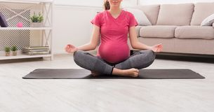 Unrecognizable pregnant woman meditating at home. Practicing yoga. Calm, relaxation, healthy pregnancy concept, copy space stock photography