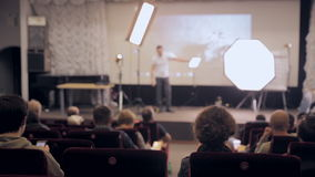 Unrecognizable public audience listening presentation. Speaker on the stage presenting products. Business traning. Concept. HD stock footage