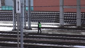 Unrecognizable railroad worker against pile of new rails and ties. 4K footage stock footage