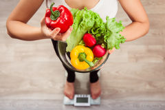 Unrecognizable rawfoodist girl checking weight on scale holding basket of fresh vegetables and green meat royalty free stock photography