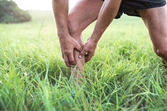Unrecognizable runner in green field. Man with injured calf. Royalty Free Stock Photography