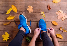 Unrecognizable runner in sports shoes tying shoelaces. Autumn le. Unrecognizable runner in blue sports shoes tying shoelaces. Colorful autumn leaves. Studio shot stock photos