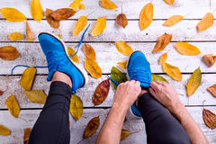 Unrecognizable runner in sports shoes tying shoelaces. Autumn le. Unrecognizable runner in blue sports shoes tying shoelaces. Colorful autumn leaves. Studio shot stock photo