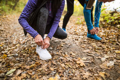 Unrecognizable runners in nature, tying shoelaces. Man with smar Royalty Free Stock Photography