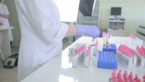 Unrecognizable scientist making laboratory analysis of blood in modern pharmacy, medical laboratory. Scientist, doctor making laboratory analysis of blood in stock video footage