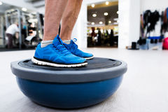 Unrecognizable senior man in gym standing on bosu balance ball. Close up of legs of senior man in gym standing on bosu balance ball and exercising as part of Stock Photography