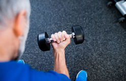 Unrecognizable senior man in gym working out with weights. Royalty Free Stock Photos