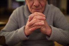 Unrecognizable senior man at home praying, hands clasped togethe. Unrecognizable senior man in gray sweater at home in his living room praying, hands clasped Stock Photography