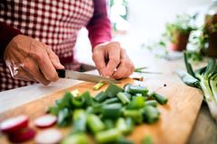A senior man preparing food in the kitchen. Royalty Free Stock Image