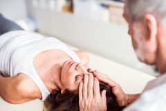 Senior physiotherapist working with a female patient. royalty free stock photo