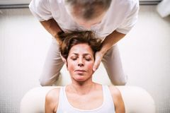 Senior physiotherapist working with a female patient. Top view. stock image