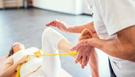 Unrecognizable senior physiotherapist working with a female patient. royalty free stock photography