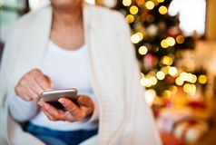 Unrecognizable senior woman in front of Christmas tree. Unrecognizable senior woman in front of Christmas tree inside the house, with smartphone, texting Royalty Free Stock Photo