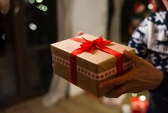 Unrecognizable woman holding a gift at Christmas time. stock photos