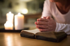 Unrecognizable senior woman praying, hands clasped together on h Stock Photos
