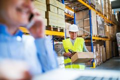 Senior woman manager with smartphone and man worker working in a warehouse. Unrecognizable senior women manager with smartphone and men worker with barcode Royalty Free Stock Photography