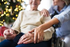 A senior woman in wheelchair with a health visitor at home at Christmas time. Unrecognizable senior women in wheelchair with a health visitor at home at royalty free stock photography