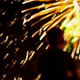 Abstract unrecognizable silhouette of boy back to us, who watches the show Fireworks. Explosive pyrotechnic devices for Stock Images