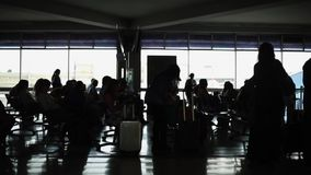 Unrecognizable silhouettes of people and luggage at airport terminal. Shot of baggage and silhouettes of people waiting at airport terminal. Shades of black and stock footage
