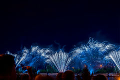 Unrecognizable Silhouettes of people watch and shoot fireworks at night. New Year holiday celebration, display, festive Royalty Free Stock Photography