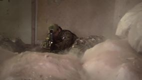 Unrecognizable soldiers under fire behind a pile of sandbags. Soldiers under fire behind a pile of sandbags clip stock video