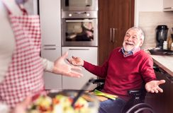 Son and senior father in wheelchair cooking in the kitchen. Unrecognizable son with his senior father in wheelchair cooking in the kitchen. Two generations Stock Photo