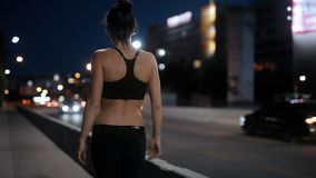 Unrecognizable sport woman go away on the bridge, back view. Unrecognizable sexy sport woman go away on the bridge at night, back view stock footage