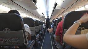 Unrecognizable stuart που περπατά στον πίνακα του αεροπλάνου και που ελέγχει τις ζώνες ασφαλείας των επιβατών μικρό ταξίδι χαρτών απόθεμα βίντεο