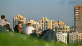 Unrecognizable teenagers hanging out in city park and listening to guitar against urbanscape. 4K long shot stock footage