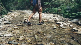 Unrecognizable Tourist With Backpack Crosses Wild River Into ford. Trek Hiking Destination Experience Lifestyle Concept. A young tourist with a backpack crosses Stock Image