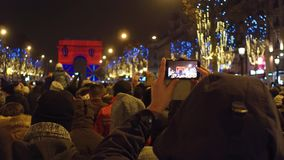 Unrecognizable tourists recording videos and shooting photos of New Year light show near famous triumphal arch, Arc de. Tourists recording videos and shooting stock video