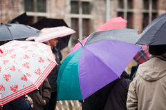 Unrecognizable tourists with umbrellas Stock Images