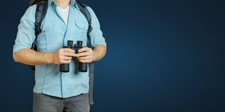 Young Traveler Man With Backpack And Binoculars Seeking Direction On Blue Background. Hiking Tourism Journey Concept. Unrecognizable Traveler Man With Backpack Stock Images