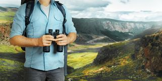 Young Traveler Man With Backpack And Binoculars Seeking Direction In Mountains. Hiking Tourism Journey Concept. Unrecognizable Traveler Man With Backpack And Royalty Free Stock Photography