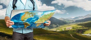 Young Traveler Man With Backpack Exploring Map In Mountains. Hiking Tourism Journey Concept. Unrecognizable Traveler Man With Backpack Exploring Map In Mountains Stock Photo