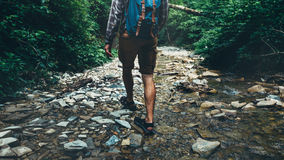 Unrecognizable Traveler Man With Backpack Walks Along Mouth Of Mountain River In Forest, Rear View. Trek Hiking Destination Experi Stock Photos