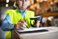 Warehouse woman worker with barcode scanner. Unrecognizable warehouse woman worker or supervisor using a mobile handheld PC with barcode scanner Stock Photo