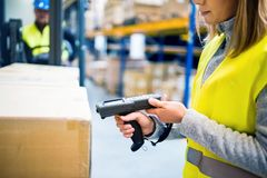 Warehouse woman worker with barcode scanner. Unrecognizable warehouse women worker or supervisor with barcode scanner. A mobile handheld PC with barcode scanner Stock Images