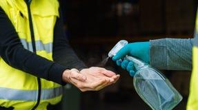 Unrecognizable warehouse workers disinfecting hands, coronavirus concept.