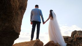 Unrecognizable wedding couple holding hands on sunset or sunrise background. Bride and groom standing outdoor near sea stock video