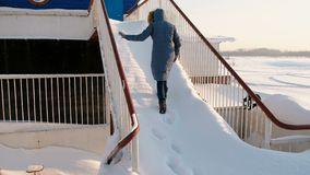 Unrecognizable woman in a blue jacket climbs up a snowy staircase. Back view. Unrecognizable woman in a blue jacket climbs up a snowy staircase. Back view stock footage