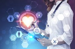 Woman doctor, medical interface with heart. Unrecognizable woman doctor standing over dark blue background with double exposure of medical interface with heart stock images