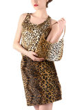 Unrecognizable woman dressed in animal print skirt and blouse, holding a bag. Jungle animal leopard print fashion style stock photo