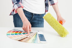 Unrecognizable woman examining palette and holding a roller Royalty Free Stock Photo