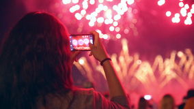 Unrecognizable woman filming colorful fireworks on his cell phone. stock footage
