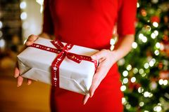 Unrecognizable woman in front of Christmas tree holding present Royalty Free Stock Image