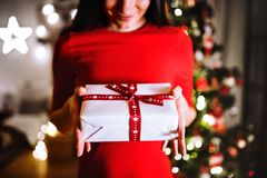 Unrecognizable woman in front of Christmas tree holding present Royalty Free Stock Photos