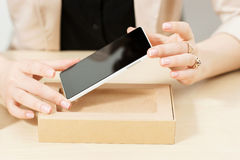 Unrecognizable woman getting new phone out of box. Female hands holding modern smartphone with blank screen . Online shopping, technology, recent gadget Royalty Free Stock Photo