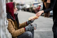 Unrecognizable woman giving food to homeless beggar man sitting in city. Unrecognizable women giving food to homeless beggar men sitting outdoors in city royalty free stock images
