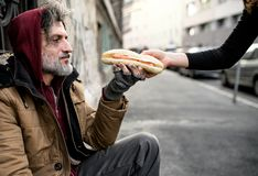 Unrecognizable woman giving food to homeless beggar man sitting in city. Unrecognizable women giving food to homeless beggar men sitting outdoors in city stock photography